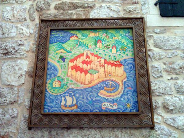 Obrázok mesta Vodice v kovovom ráme, dole pod ním je ukrytá spomínaná keška.